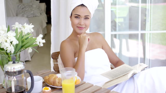 Gorgeous young woman relaxing with a book Gorgeous young woman relaxing with a book as she enjoys her breakfast on an outdoor patio wrapped in a clean white towel wearing a towel stock videos & royalty-free footage