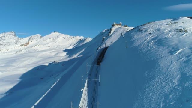 stockvideo's en b-roll-footage met gornergrat berg-en tandradtrein in zonnige winterse dag. luchtfoto. zwitserse alpen, zwitserland - matterhorn