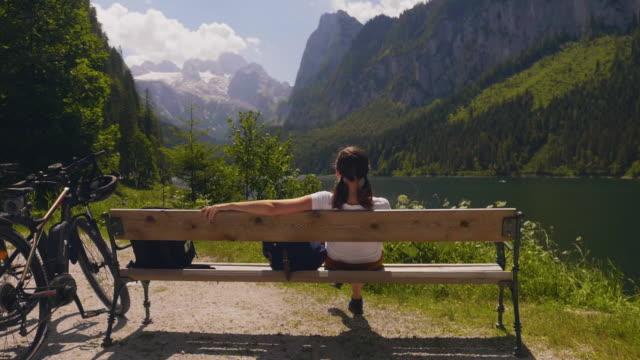 Gosausee Österreich, sitzt die junge Frau auf Bank Berglandschaft – Video