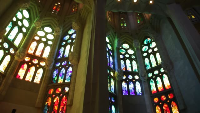 Gothic church interior with coorful stained glasses Panning at gothic church interior with colorful stained glasses. Dark and spiritual ambiance gothic architecture stock videos & royalty-free footage