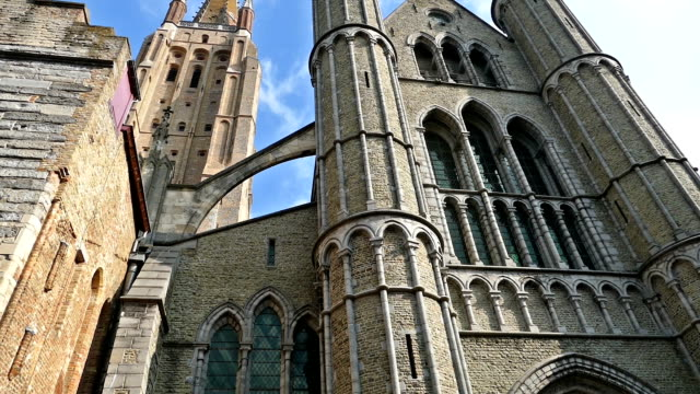 Gothic facade and tall belfry of the Church of Our Lady, Bruges video