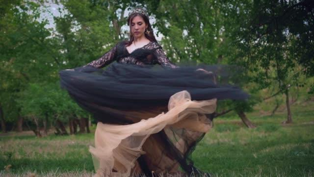 gotisk drottning i svart vintage flygande klänning i en mörk skog. tyg fladdrande - aftonklänning bildbanksvideor och videomaterial från bakom kulisserna