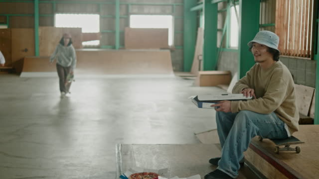 goup von jungen japanischen skateboarder essen pizza während skateboard-session - teenage friends sharing food stock-videos und b-roll-filmmaterial