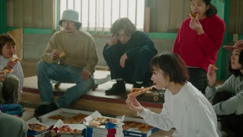vídeos y material grabado en eventos de stock de goup de jóvenes skaters japoneses comiendo pizza durante la sesión de skateboard - actividades recreativas