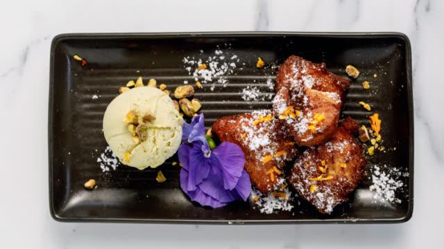 gourmet dessert - ricotta doughnuts with pistachio gelato - decorazione per dolci video stock e b–roll