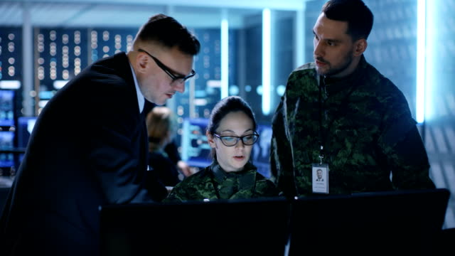 vídeos de stock e filmes b-roll de govenment surveillance agency and military joint operation. male agent, female and male military officers working at system control center. - controlo