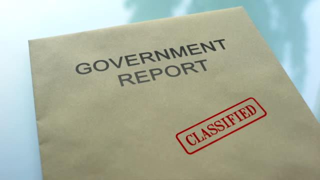 政府の報告書、分類で、重要な書類をフォルダーにシールをプレス - クラシファイド広告点の映像素材/bロール