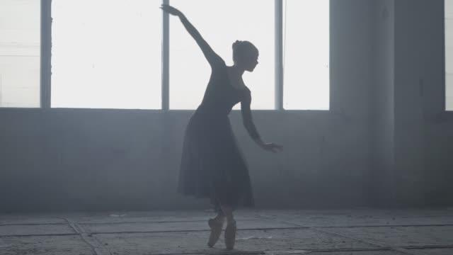graciös ballerina dansar i svart klänning i studion framför ett stort fönster. - piruett bildbanksvideor och videomaterial från bakom kulisserna