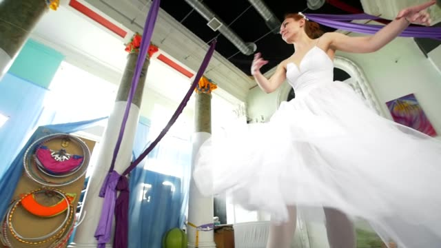 Graceful ballerina in white dress performs dance in spacious white studio Graceful ballerina in white dress performs dance in spacious white studio, slow motion tulle netting stock videos & royalty-free footage