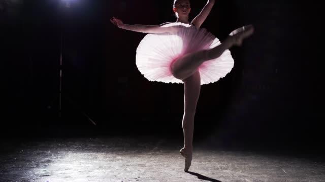 graciösa flexibla ballerina dans på hennes pointe balettskor i rampljuset på svart bakgrund i studio. flicka visar klassisk balett pas tutu och pointe skor. - piruett bildbanksvideor och videomaterial från bakom kulisserna