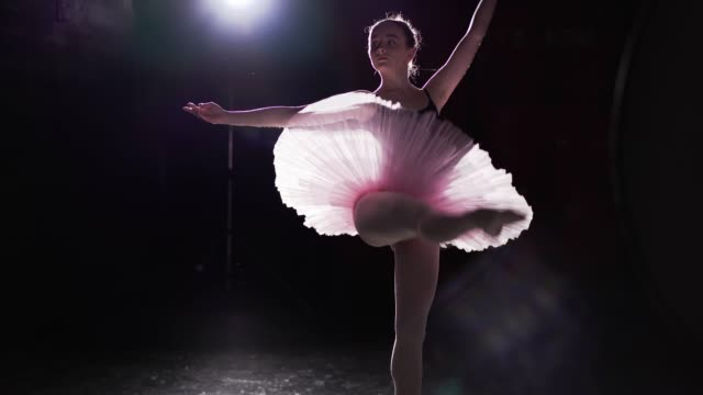 graciösa flexibla flicka dansa på hennes pointe balettskor i rampljuset på svart bakgrund i studio. professionell ballerina visar klassisk balett pas tutu och pointe skor. - piruett bildbanksvideor och videomaterial från bakom kulisserna
