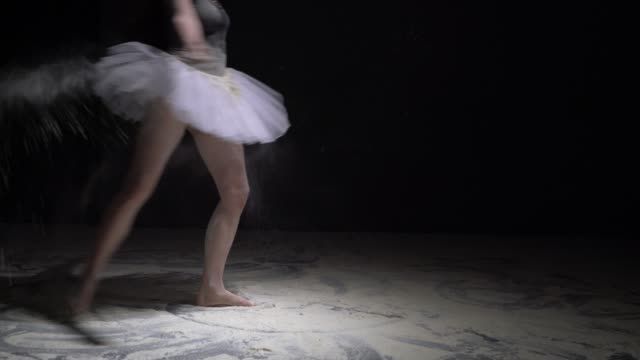 暗闇の中でほこりを投げるチュチュの優雅な女の子 ビデオ