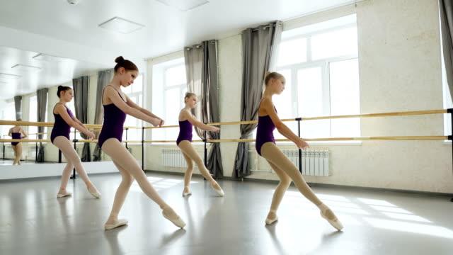 美しいレオタードで優雅な小さなバレエ ダンサー ライト スタジオでの練習の動きを行使しています。可愛い女の子が同時に一緒に動いています。 - ダンススタジオ点の映像素材/bロール