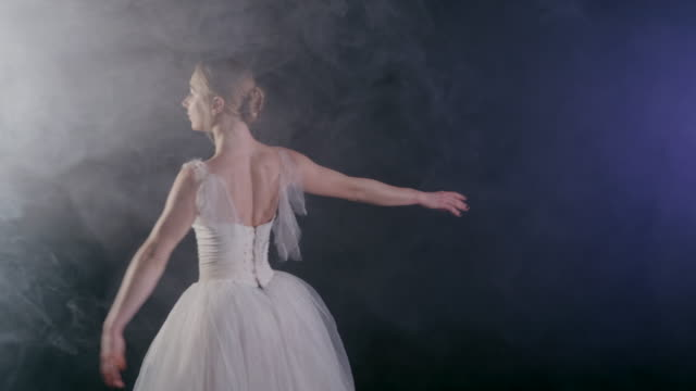 graceful sensual ballerina in white tutu dress dancing elements of classical or modern ballet in the dark with light and smoke on the black background, 4k video