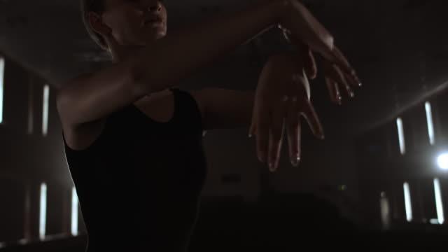 煙の中の劇場の暗いステージに暗いドレスで優雅な女性バレリーナは、スローモーションでダンスの動きを実行します - チュチュ点の映像素材/bロール