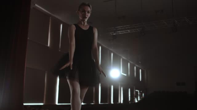 graciösa kvinna ballerina i en mörk klänning på en mörk scen av teatern i röken utför danssteg i slow motion - piruett bildbanksvideor och videomaterial från bakom kulisserna