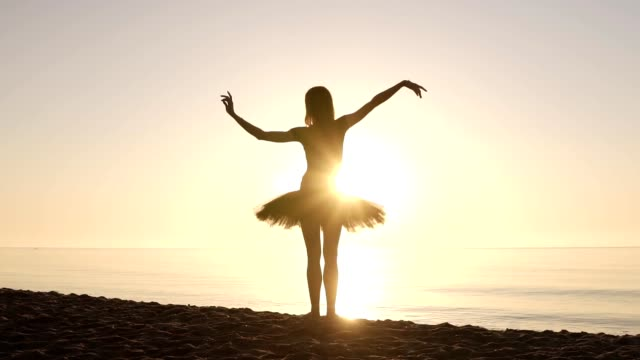 graceful young girl in ballet tutu standing on a coastline facing to the sea. waving her hands. doing ballet moves. sun shines. backside view - tutù video stock e b–roll
