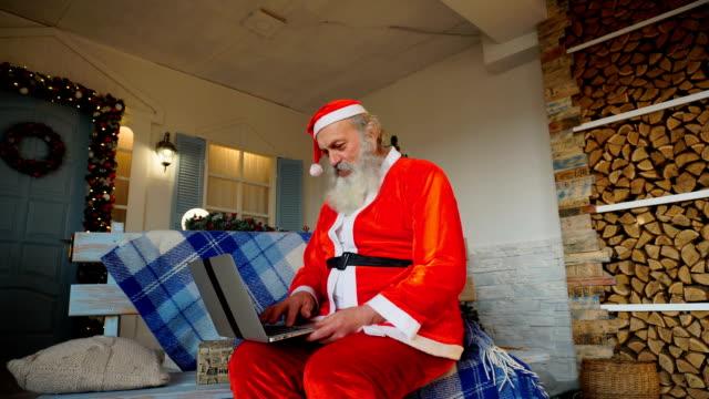 Gracious Santa Claus working on laptop video