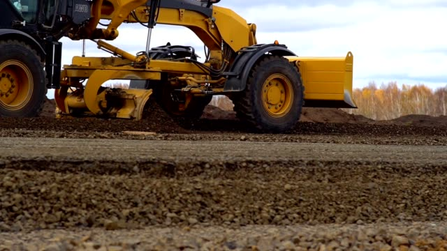 Grader aligns and lays the ground on the road. Grader aligns and lays the ground on the road. Close-up, slow motion. construction vehicle stock videos & royalty-free footage