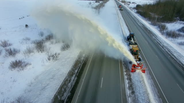 Grader clean remove snow, snowplow, snow blower, blast snowfall, winter, road, special vehicle on the highway, cool frozen fountain of snow aerial view Orange yellow grader clean remove snow, snowplow, snow blower, blast, snowfall, winter, road, special vehicle on the highway, cool frozen fountain of snow, aerial orbit view plow stock videos & royalty-free footage