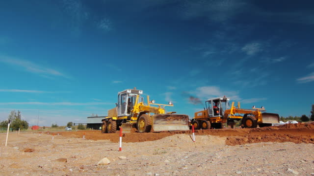 grader leveling ground on construction site before kick off building project - industria edile video stock e b–roll
