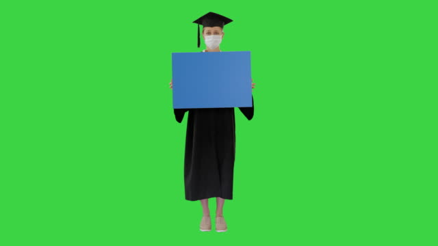 Graduate student girl in protection mask holding blank board on a Green Screen, Chroma Key