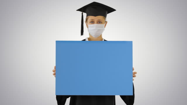 Graduate student girl in protection mask holding blank board on gradient background