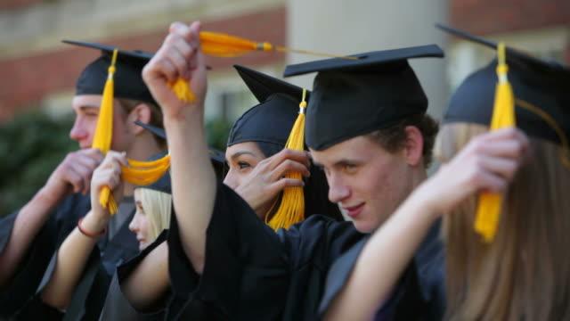 graduates move tassels and celebrate - kep şapka stok videoları ve detay görüntü çekimi