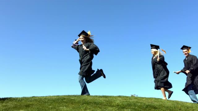 laureati in esecuzione sulla collina al rallentatore - tocco accademico video stock e b–roll