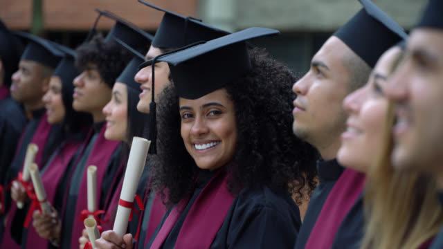 stockvideo's en b-roll-footage met gediplomeerden die zich in een lijn bij de graduatieceremonie bevinden die weg kijkt terwijl de afro jonge vrouw camera het glimlachen bekijkt - student