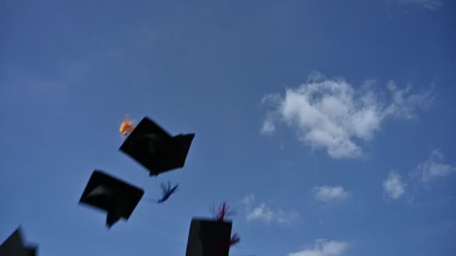 i laureati gettano un cappello nero nel cielo per esprimere la loro gioia alla laurea. - berretto video stock e b–roll