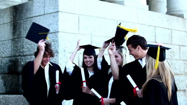 graduates throwing mortar boards in the air - kep şapka stok videoları ve detay görüntü çekimi