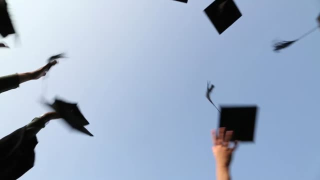 Graduation caps are tossed into the air by a happy asian girls group friends