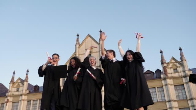 vídeos de stock, filmes e b-roll de os tampões da graduação são jogados no ar por um grupo feliz de amigos do estudante - beca