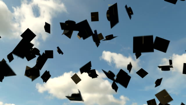 Graduation hats in the air on the blue sky background, university graduation video