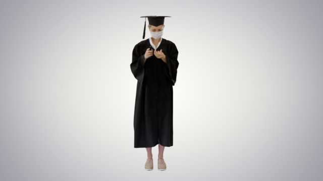 Graduation student in medical mask using sanitizer on gradient background
