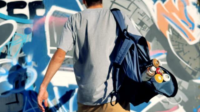 グラフィティ アーティストは、壁に白いペンキを追加します。 - street graffiti点の映像素材/bロール