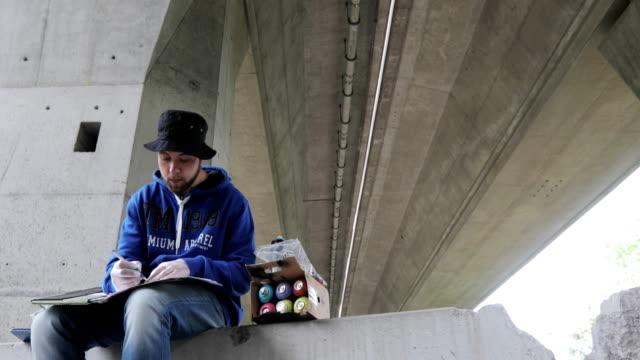 Graffiti Artist Drawing a Sketch Before Spraying on Wall