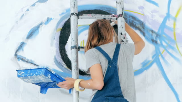 Graffiti Artist Drawing face of beautiful woman and eye with paint on Street Wall. Female working with brush. Urban Outdoors Art Concept. Slow motion