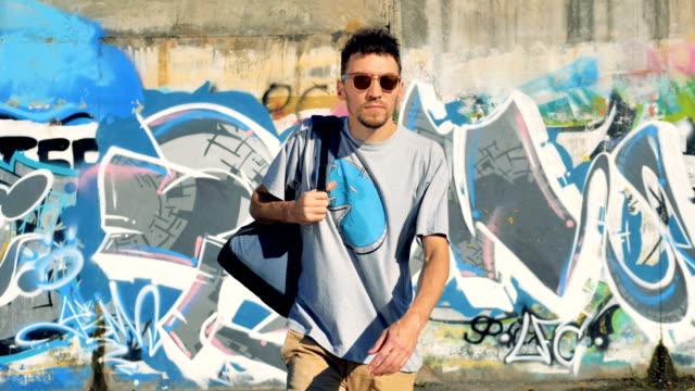 Graffiti-Künstler packt seinen Rucksack und geht auf die Kamera. – Video