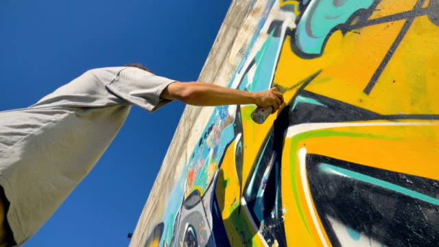 Graffiti artist is painting a yellow letter on the wall, view from below. video
