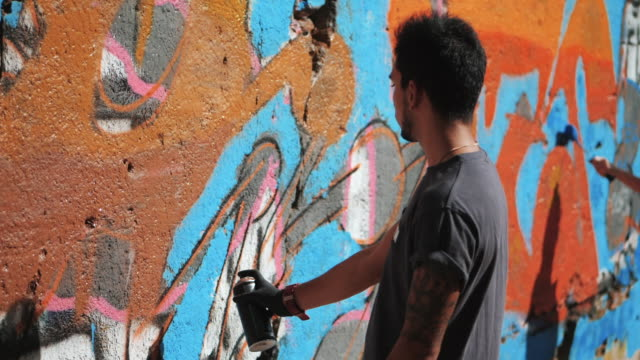 Graffiti Artist Painting On The Street Wall. Handsome Man with aerosol spray bottle spraying with colorful paint, Urban Outdoors Art Concept. Slow motion video