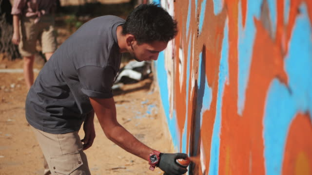 Graffiti Artist Painting On The Street Wall. Handsome Man with aerosol spray bottle spraying with colorful paint, Urban Outdoors Art Concept. Slow motion. Side view video