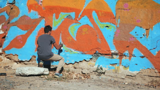 Graffiti Artist Painting On The Street Wall. Handsome Man with aerosol spray bottle spraying with colorful paint, Urban Outdoors Art Concept. Slow motion. Back view, overall plan video
