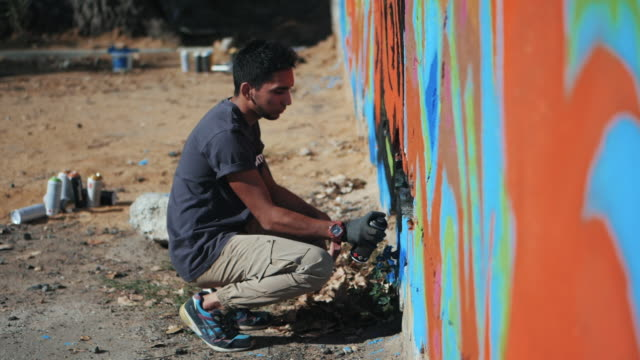 Graffiti Artist Painting On The Street Wall. Handsome Man with aerosol spray bottle spraying with colorful paint, Urban Outdoors Art Concept. Slow motion. Gimbal shot. Side view video