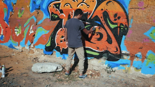 Graffiti Artist Painting On The Street Wall. Handsome Man with aerosol spray bottle spraying with colorful paint, Urban Outdoors Art Concept. Slow motion. Gimbal shot video