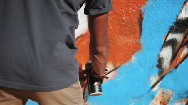 Graffiti Artist Painting On The Street Wall. Male hand with aerosol spray bottle spraying with colorful paint, Urban Outdoors Art Concept. Slow motion. Close up view video