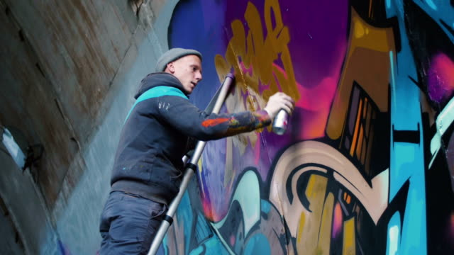 Graffiti artist painting on the wall, exterior Graffiti artist painting on the wall, exterior mural stock videos & royalty-free footage
