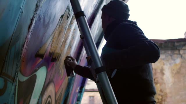 graffitikonstnär måla på väggen, exteriör - väggmålning bildbanksvideor och videomaterial från bakom kulisserna