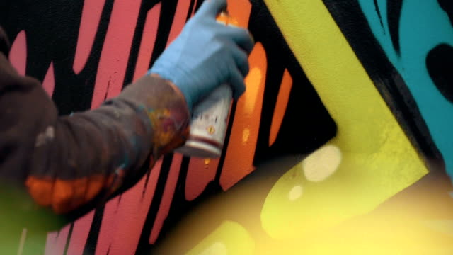 Graffiti artist painting on the wall, interior, close up video